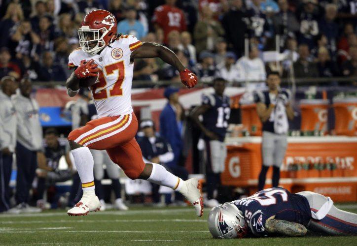 Kansas City Chiefs running back Kareem Hunt (27) eludes New England Patriots defensive end Cassius Marsh (55) as he scores a touchdown on Thursday in Foxborough, Mass. (AP Photo/Steven Senne)