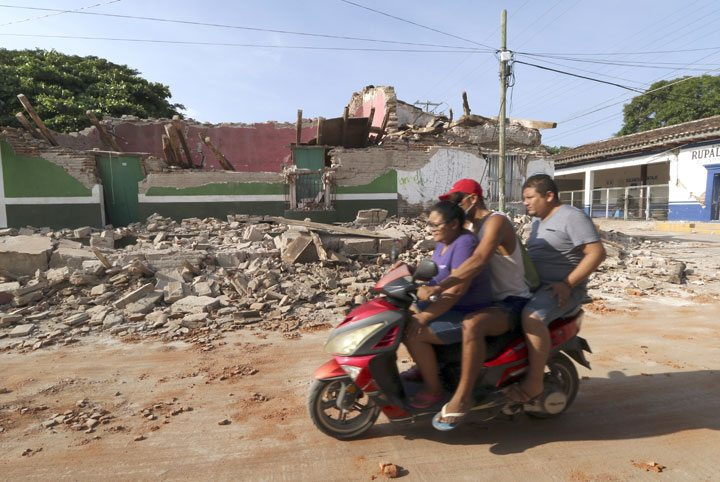 Residents Friday drive by a collapsed building felled by a massive earthquake in Juchitan, Oaxaca state, Mexico. One of the most powerful earthquakes ever to strike Mexico has hit off its southern Pacific coast, killing at least 32 people, toppling houses, government offices and businesses. (AP Photo/Luis Alberto Cruz)