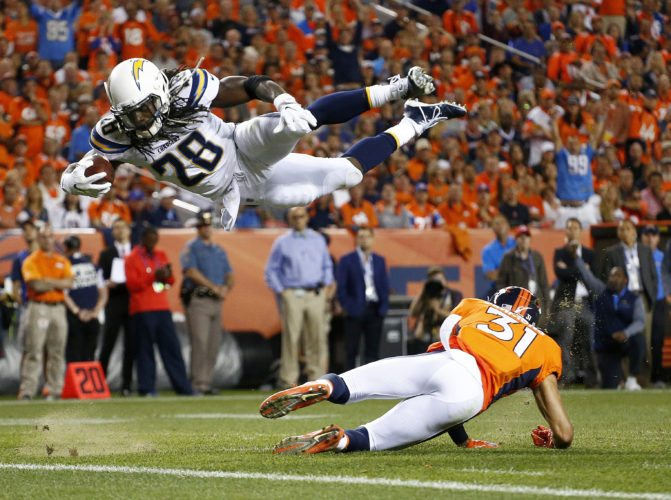 Los Angeles Chargers running back Melvin Gordon (28) dives over Denver Broncos strong safety Justin Simmons (31) on Monday in Denver. (AP Photo/Jack Dempsey)