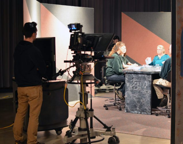 "A view from behind the teleprompter at a live broadcast of ""Ask the DNR"" shows Michigan Department of Natural Resources staffers Monica Joseph, Jennifer Johnson and Doug Barry, with host Ann Feldhauser seated at the center of the table."