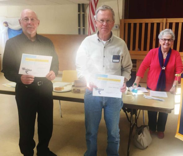 From left, Larry Yarck and Jim Benzing receive their membership certificates. In the background is Orice Walters, chairwoman for the month.