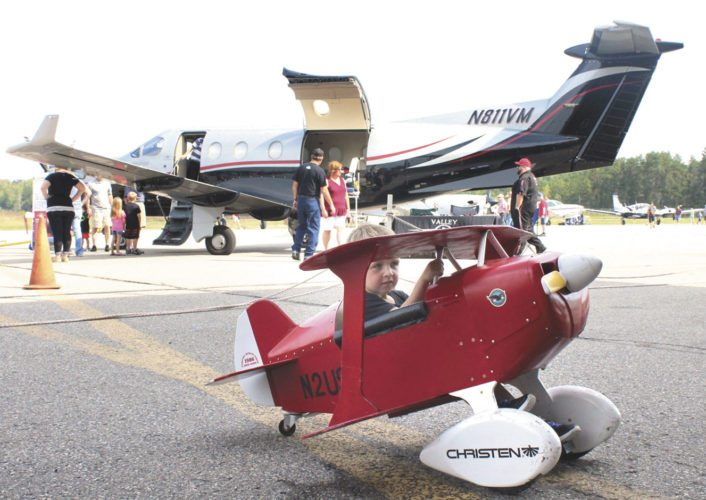 The Ford Airport Day drew crowds Saturday to see both aircraft and classic cars. Jaxson Pawlak of Iron Mountain rides a mini airplane bike around the airport grounds.