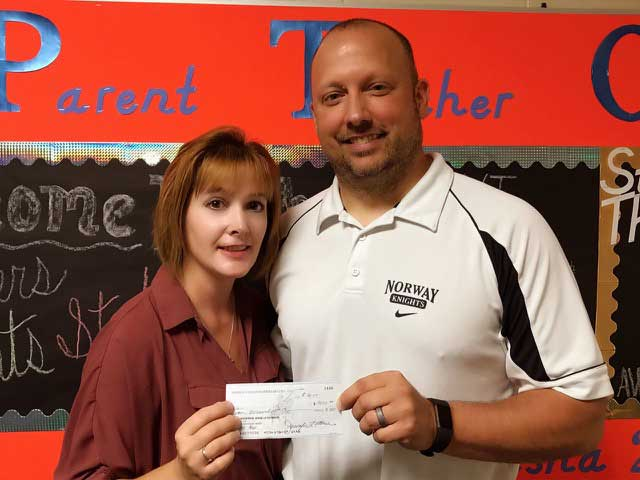 Presenting a check for $7,000 for technology is Tasha DeBernardi of the Norway PTO to Norway Principal Rico Meneghini.