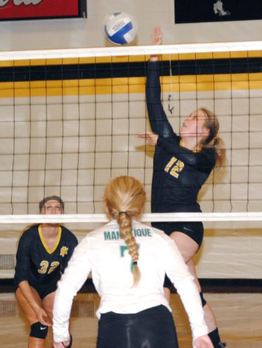Iron Mountain's Claire Czernek (12) goes up for a kill against Manistique on Thursday. (Burt Angeli/The Daily News)