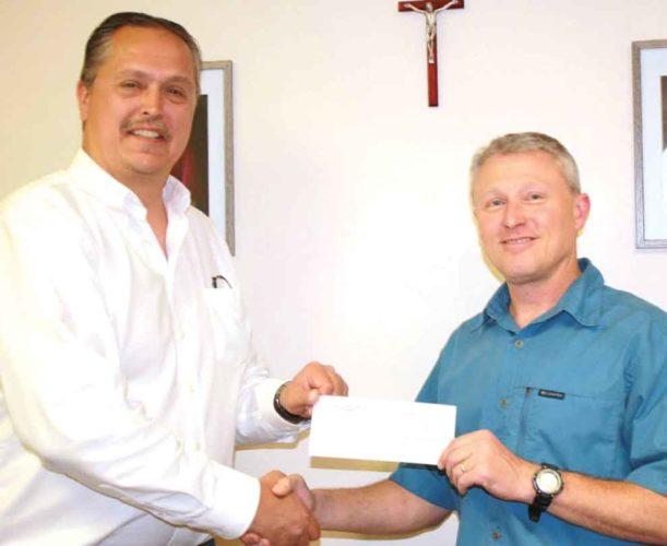 FOR BEING A Lumen Christi nominee, Mike Malnar, left, accepts a check for $1,000 from Catholic Extension on behalf of Alpha Omega House in Iron Mountain. Presenting the check is Kyle Rambo, right, executive director of Catholic Social Services of the Upper Peninsula.