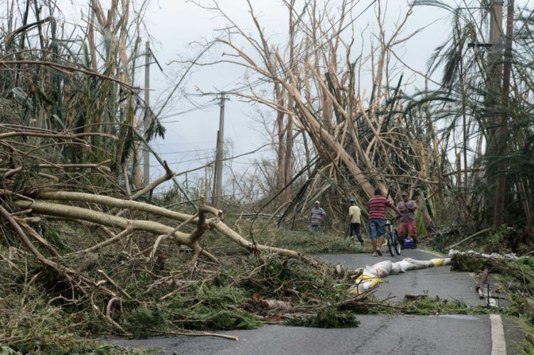 LOCALS HELP CLEAR debris from a road Thursday after the passing of Hurricane Maria, in Yabucoa, Puerto Rico. The Category 3 storm was expected to approach the Turks and Caicos Islands and the Bahamas by early today.  (AP Photo/Carlos Giusti)