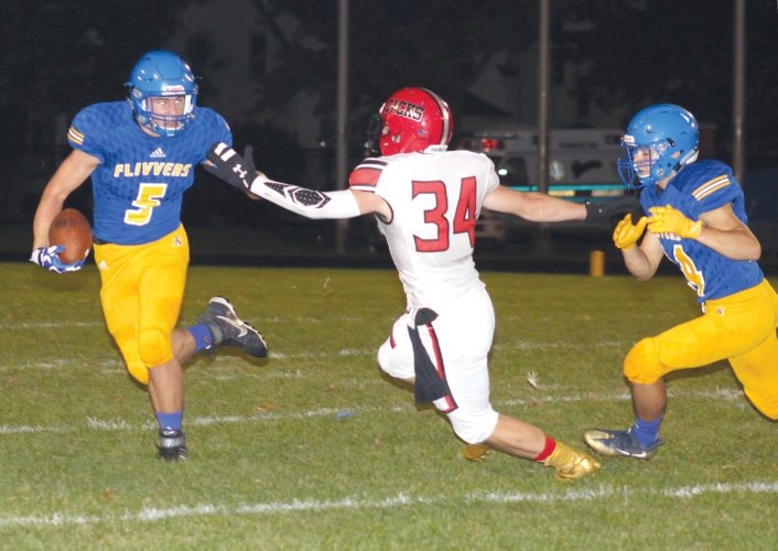 Kingsford's Tyler Beauchamp (5) slips past Wausau East's Tyler Tate (34) in Friday's non-conference game at Flivver Field. (Theresa Proudfit/The Daily News)