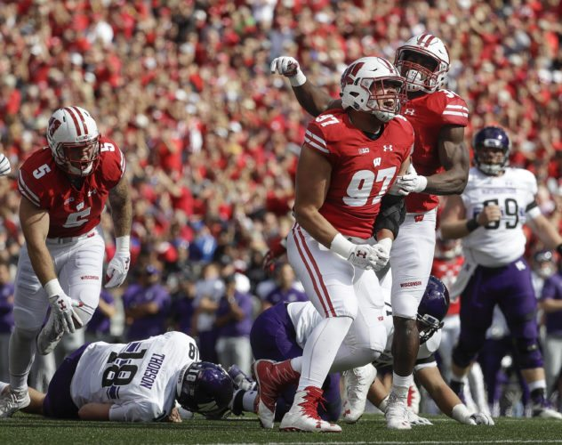 Wisconsin's Isaiahh Loudermilk (97) and Leon Jacobs celebrate after a sack of Northwestern quarterback Clayton Thorson (18) on Saturday in Madison, Wis. Ninth-ranked Wisconsin is turning up the pressure. After swarming Northwestern for eight sacks, the Badgers have their sights set on Nebraska this weekend. (AP Photo/Morry Gash)