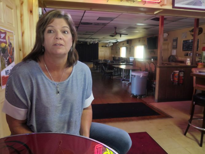 Tammy Graceffa, 51, owner of the Hiawatha Bar and Grill, talks in her restaurant on Wednesday, Oct. 4, 2017 in Sturtevant, Wis., about Foxconn's announcement of the location of its planned manufacturing plant in nearby Mount Pleasant. Graceffa owns land in the development site and said the news was bittersweet because she stands to benefit economically but she might lose the land where she grew up. (AP Photo/Ivan Moreno)