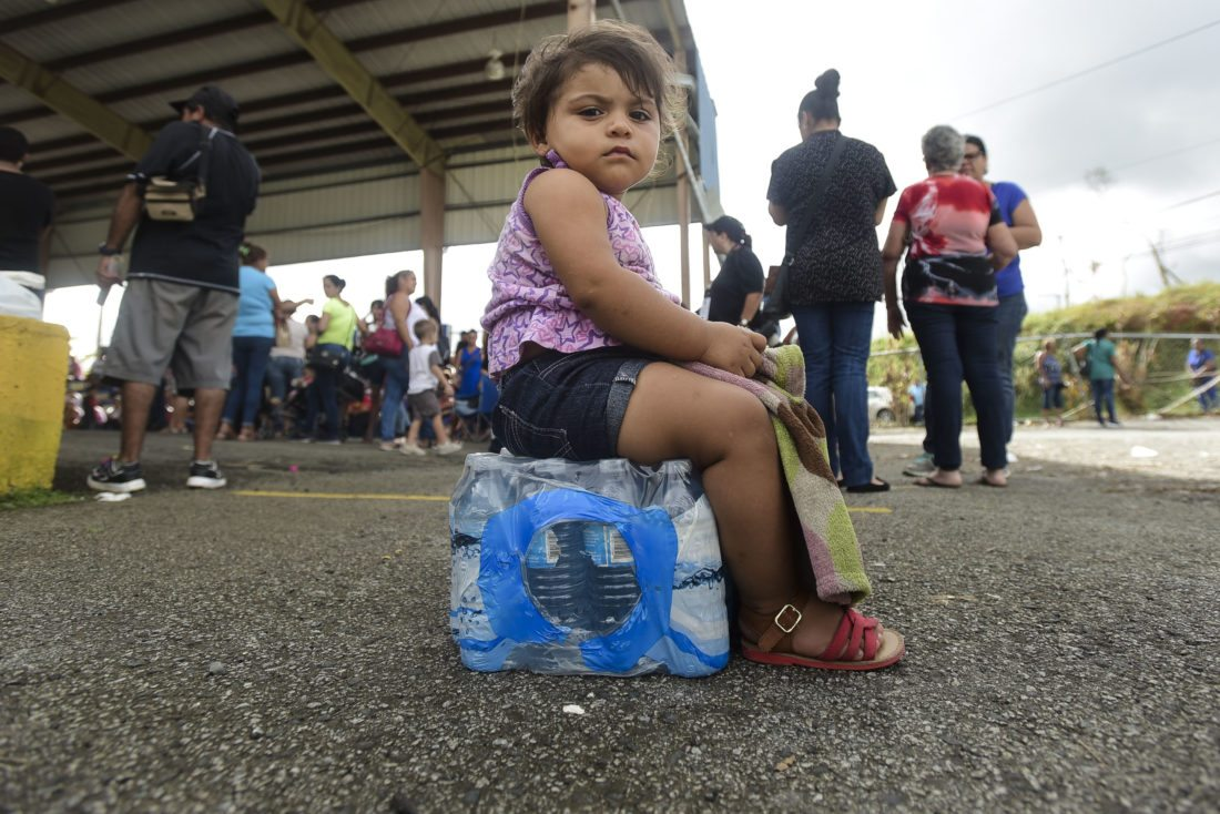 Kerialys Aldea de Jesus sits on bottled water earlier this week at the Jose de Diego Elementary School where residents file FEMA forms for federal aid in the aftermath of Hurricane Maria in Las Piedras, Puerto Rico. (AP Photo)