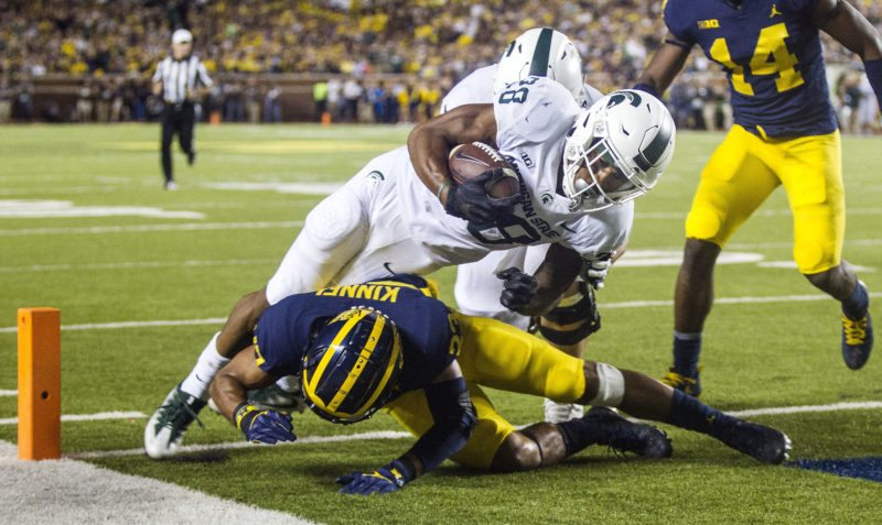 Michigan State running back Madre London, center, dives over Michigan defensive back Tyree Kinnel, bottom, to score a touchdown in Ann Arbor, Mich. on Saturday. (AP Photo/Tony Ding)