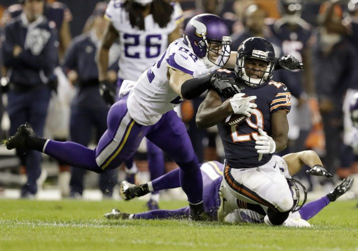 Minnesota Vikings free safety Harrison Smith (22) and strong safety Andrew Sendejo (34) tackle Chicago Bears running back Tarik Cohen (29) on Monday in Chicago. (AP Photo/Darron Cummings)