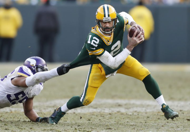 FILE - In this Dec. 24, 2016, file photo, Green Bay Packers' Aaron Rodgers tries to get out of the grasp of Minnesota Vikings' Anthony Barr during the second half of an NFL football game in Green Bay, Wis. Rodgers expresses admiration and respect for Minnesota's defense under Mike Zimmer, one of the few coaches who've had some success in thwarting Green Bay's exceptional quarterback. But Zimmer has his own anxiety about preparing for and playing against Rodgers. (AP Photo/Matt Ludtke, File)