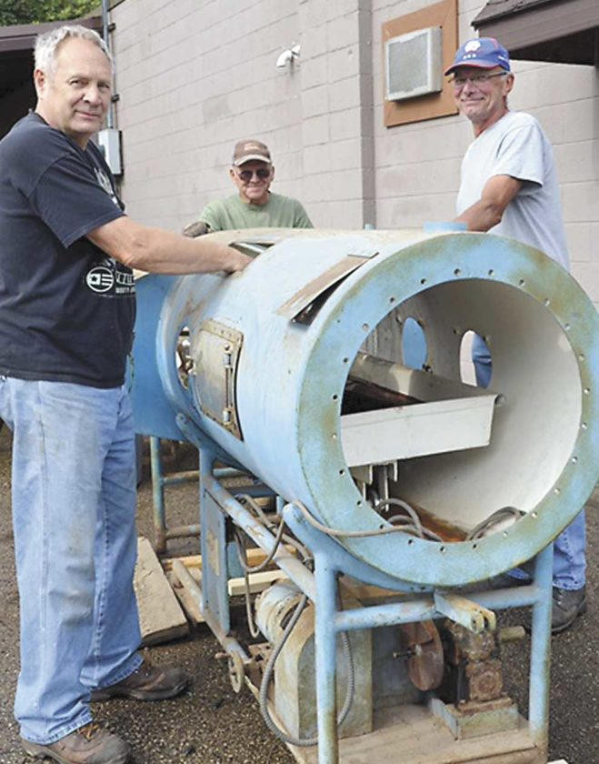 FROM LEFT, ARNE Haavisto, Joe Geldmeyer and Gary Kassens pose with the iron lung, built by Kimberly Clark Mill workers and Niagara vocational students in 1941, that is being restored for the Niagara Historical Museum in Niagara, Wis. (Karen Klenke photo)