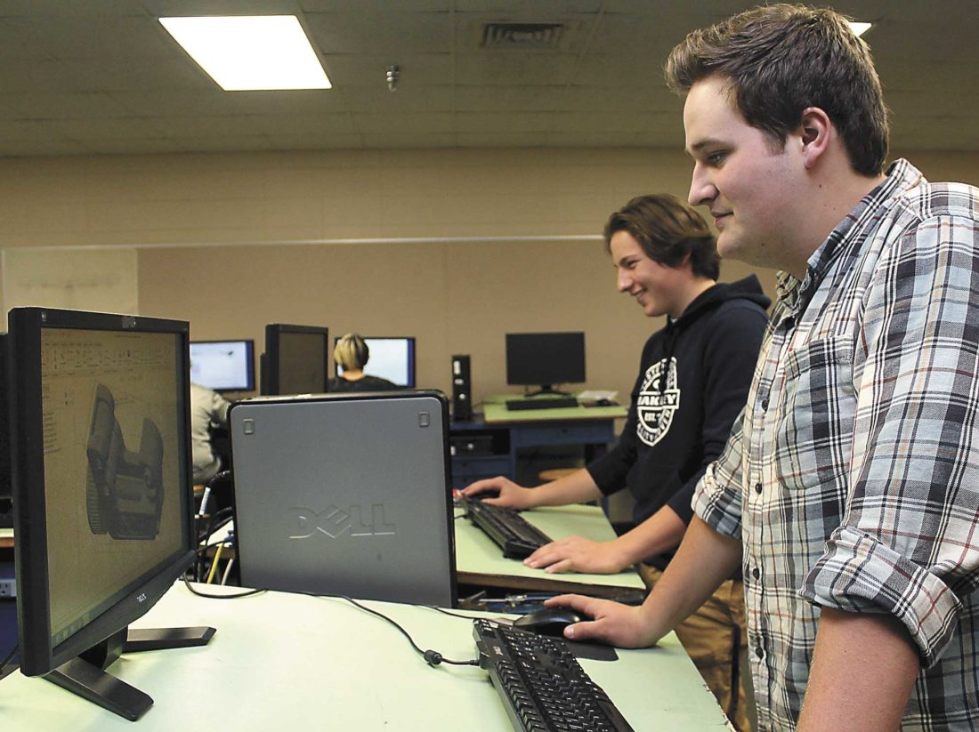KINGSFORD HIGH SCHOOL students Ben Anderson and Allen Linn work on assignments in CAD class. (Theresa Proudfit/ Daily News photo)