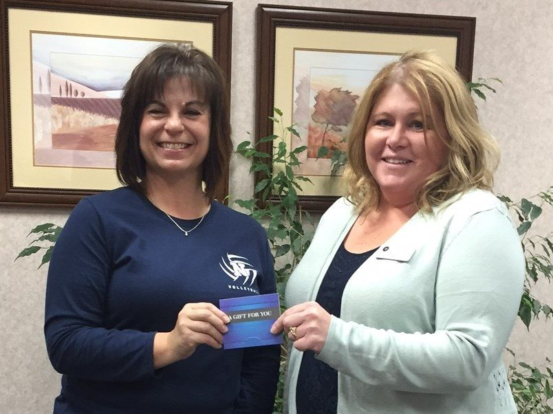 NORTHERN INTERSTATE BANK customer service representative Becky Aderman, right, presents Suzie Sheski of Norway with her $50 travel card from the SHAZAM Escape to Rewards debit card promotion.