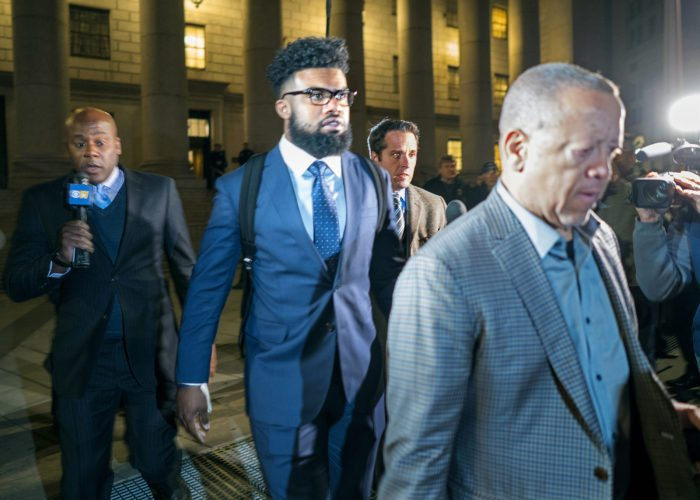 Dallas Cowboys star Ezekiel Elliott, center, exits federal court after a hearing Monday in New York. Elliott is seeking to have his six game suspension by the NFL postponed. (AP Photo/Craig Ruttle)