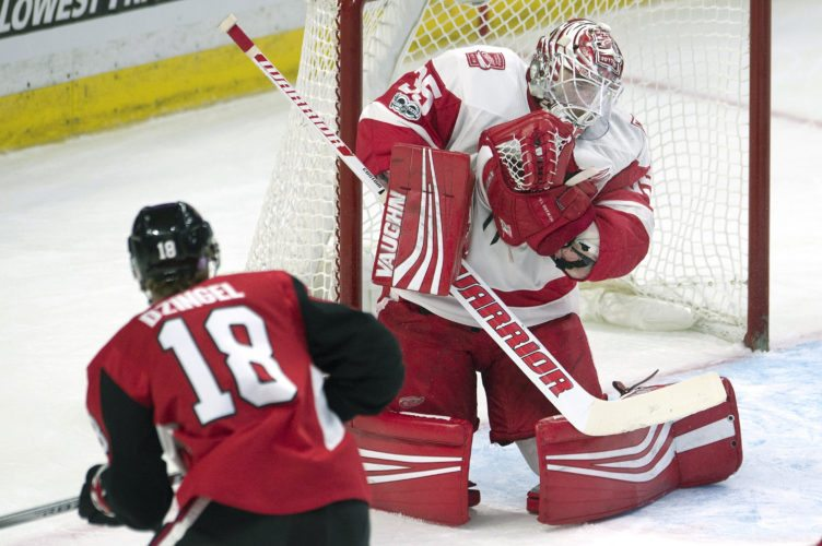 Detroit Red Wings goalie Jimmy Howard, right, makes a save on a shot from Ottawa Senators left wing Ryan Dzingel during the first-period on Thursday in Ottawa, Ontario. (Adrian Wyld/The Canadian Press via AP)