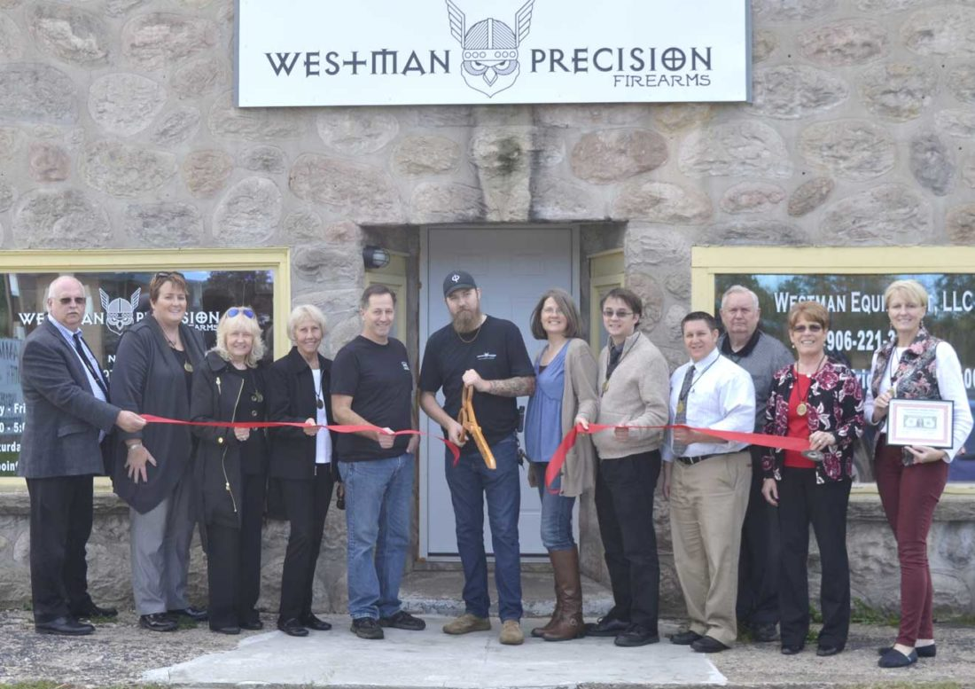 A RIBBON-CUTTING ceremony took place recently at Westman Precision Firearms with ambassadors from the Dickinson Area Chamber Alliance in attendance — from left are ambassadors Corky DeRoeck, Trisha Peterson, Patti Schneider and Greta Michaud; Tom Westman, Tommy Westman and Theresa Westman of Westman Precision Firearms; and ambassadors Teddy Izzo, Ben Ryan, Joe Testolin, Lynda Zanon and Suzanne Anderson. Chris Tomassucci/Daily News photo