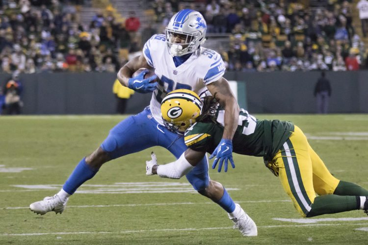 Detroit Lions running back Dwayne Washington (36) runs with the ball as Green Bay Packers cornerback Davon House (31) makes a tackle during a game on Monday in Green Bay, Wis. (Adam Niemi/Iron Mountain Daily News)