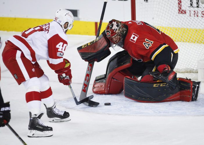 Detroit Red Wings' Henrik Zetterberg, left, tries to get the puck past Calgary Flames goalie Mike Smith on Thursday in Calgary, Alberta. (Jeff McIntosh/The Canadian Press via AP)