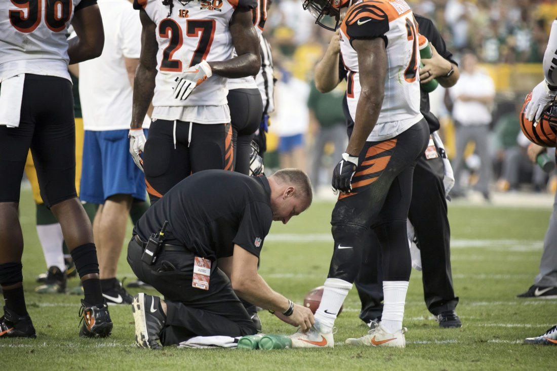 Jon Jungwirth, kneeling, ties Darqueze DennardÕs shoe during a game against the Green Bay Packers on Sunday, Sept. 24, 2017, in Green Bay, Wis. (Adam Niemi/Iron Mountain Daily News)