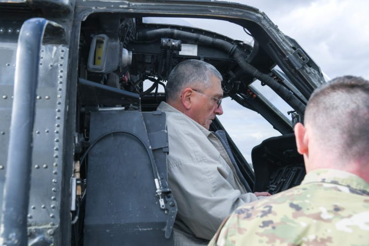 DANIEL PAUL, ACCOMPANIED by Spc. Catlin Cone at Fort Campbell, Kentucky, examines the controls of a Blackhawk helicopter.