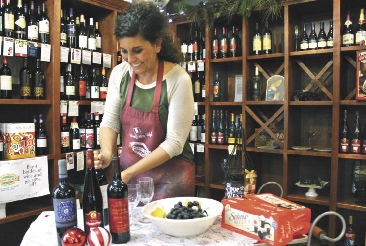 LISA BERLINSKI, CO-OWNER of Crispigna's Italian Market, gets the wine-tasting display ready for the annual Girls' Night Out from 5 to 8 p.m. Thursday in Iron Mountain. Crispigna's will offer wine tasting, Italian appetizers, food samples starting at 5:30 p.m., wine specials, gift baskets and gift certificates for sale, plus have a drawing for an Italian dinner. (Theresa Proudfit/Daily News photo)