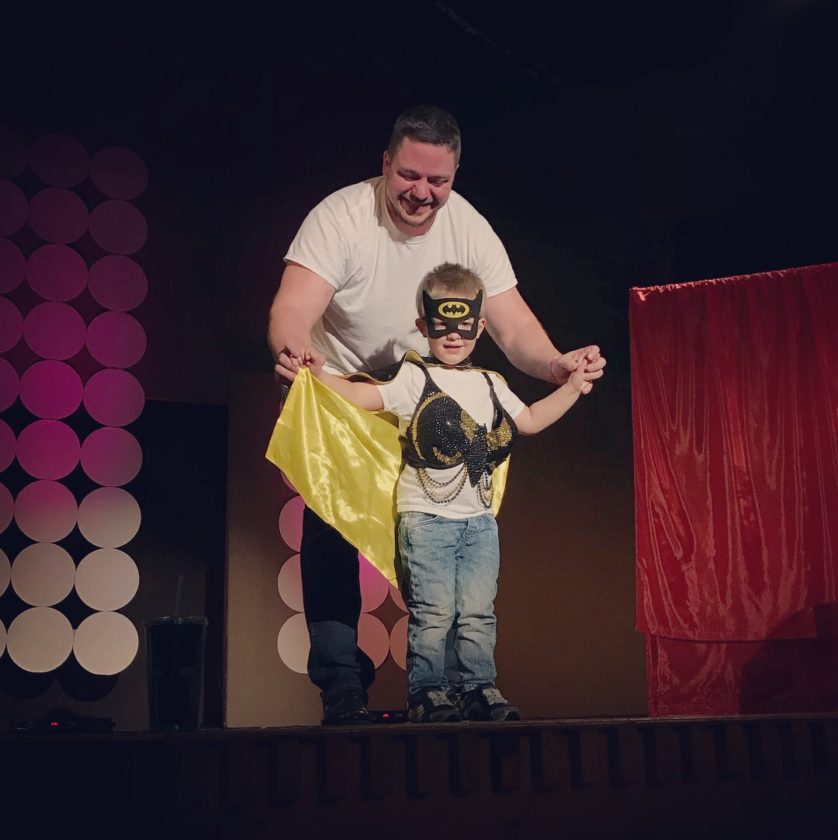 """Cale Anderson assists his nephew Grady Anderson modeling """"Holy Boobies Batman,"""" created by Mel Bashaw for Bras for a Cause."""