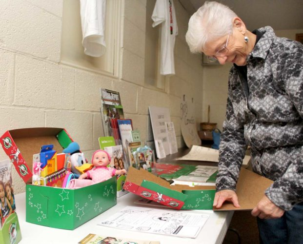 Marion Marsden, coordinator of the Iron Mountain Operation Christmas Child drop off site, prepares a display at the First Covenant Church in Iron Mountain.  Theresa Proudfit/Daily News photo