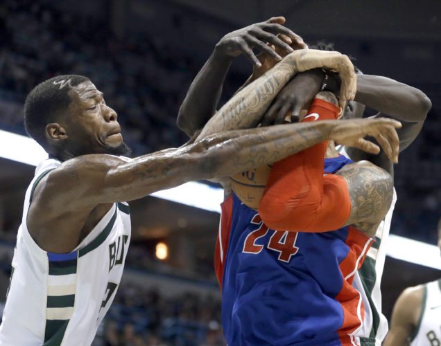 Milwaukee Bucks' DeAndre Liggins, left, and Thon Maker, back, attempt to steal the ball from Detroit Pistons' Eric Moreland (24) on Wednesday, Nov. 15, 2017, in Milwaukee. (AP Photo/Aaron Gash)