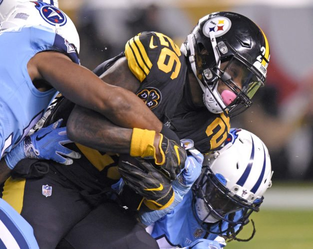 Pittsburgh Steelers running back Le'Veon Bell (26) is tackled by Tennessee Titans nose tackle Austin Johnson, left, and Johnathan Cyprien, right, after a short gain on Thursday in Pittsburgh. (AP Photo/Don Wright)