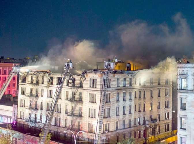 AP Photo/Andres Kudacki Firefighters battle a large fire on the top floors of an apartment building in New York City's Harlem neighborhood Friday.