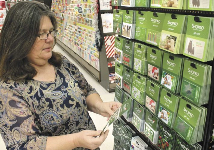 Grace Michaud of Spread Eagle, Wis., founder of the Niles Hiltunen Benefit Fund, shops for gift cards after learning the charity had been awarded more than $20,000 from 100-Plus Women Who Care of Dickinson County on Tuesday evening.   (Theresa Proudfit/Daily News Photo)