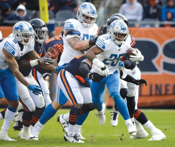 Detroit Lions running back Theo Riddick (25) tries to break away from Chicago Bears defense on Sunday in Chicago. (AP Photo/Nam Y. Huh)