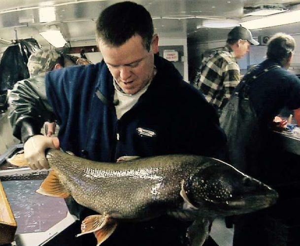Brad Ray, a Wisconsin Department of Natural Resources fisheries biologist, holds a lake trout estimated to be at least 46 years old. (David Stokes/Wisconsin DNR Photo)