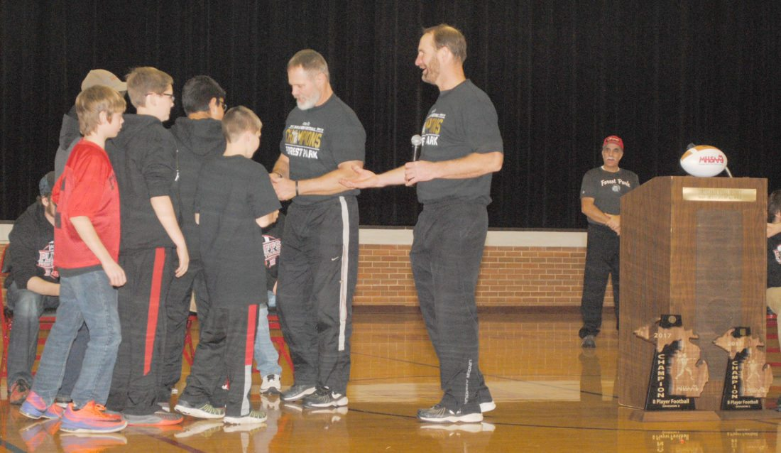 "Burt Angeli/The Daily News Photo  Forest Park head coach Dave Graff, right, and assistant Gerard Valesano distribute state championship gold medals to managers Payton Woollard, Adrian Bruette, Hunter Loehr, Ethan Williams and Will Curtis during the welcome home celebration Saturday night in Eddie Chambers Gymnasium. ""You are the next chapter in Forest Park football,"" Graff told the managers."