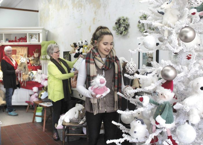 Linnea Marchetti and Kristine Cohodas set up Christmas displays as Tori Peterson shops for gifts at Linnea & Kristine in downtown Iron Mountain. The floral and gift shop is starting its 25th year of business and is offering a 15 percent discount storewide for Small Business Saturday. (Theresa Proudfit/Daily News Photo)