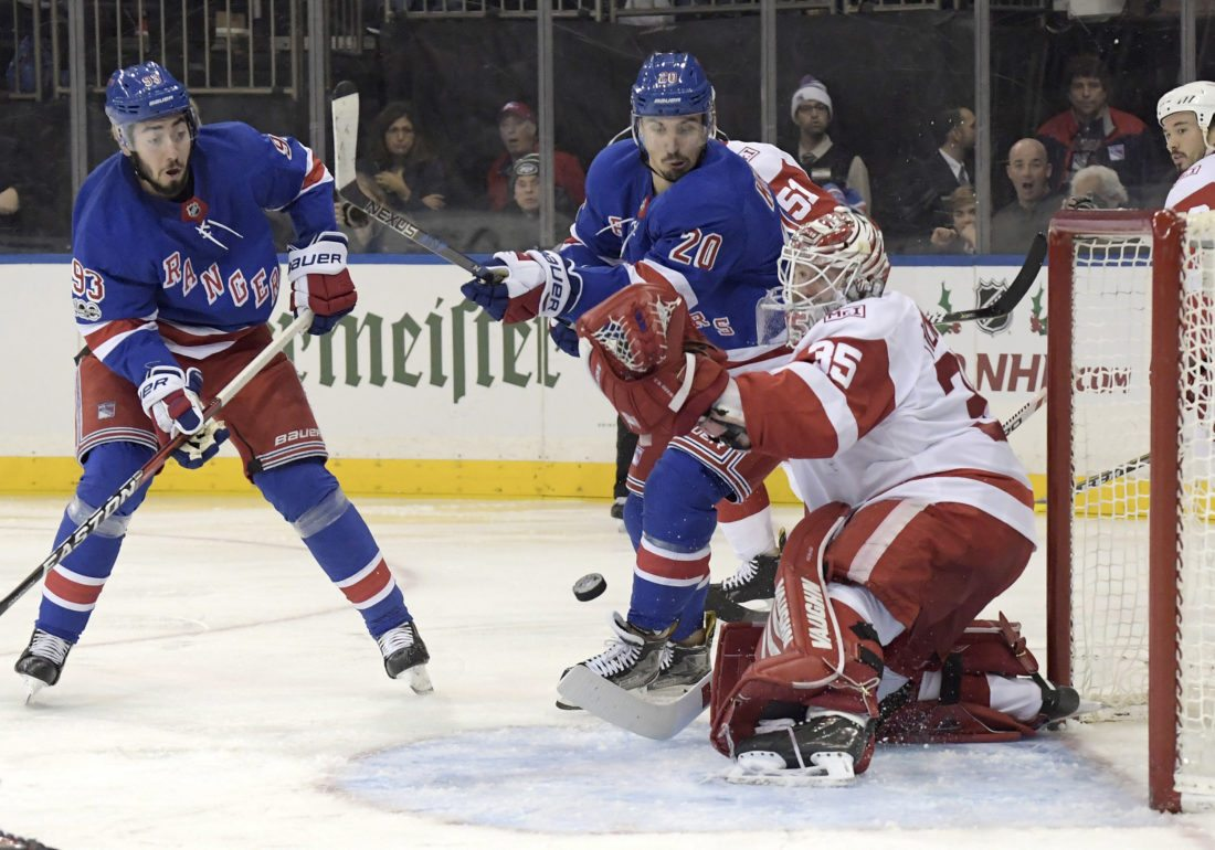 New York Rangers left wing Chris Kreider and center Mika Zibanejad (93) eye the puck as it is deflected by Detroit Red Wings goalie Jimmy Howard (35) on Friday, Nov. 24, 2017, at Madison Square Garden in New York. (AP Photo/Bill Kostroun)