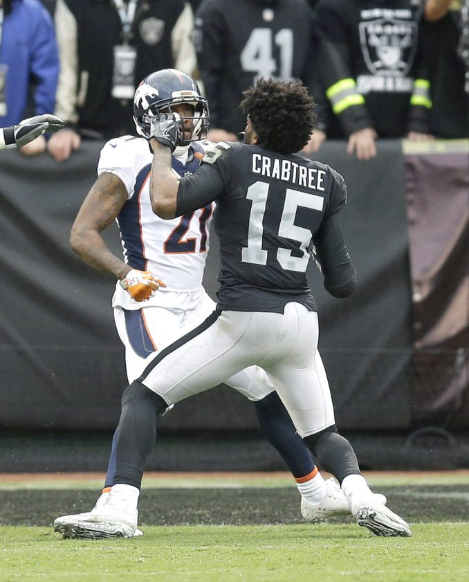 Denver Broncos cornerback Aqib Talib (21) fights Oakland Raiders wide receiver Michael Crabtree (15) on Sunday in Oakland, Calif. (AP Photo/Ben Margot)