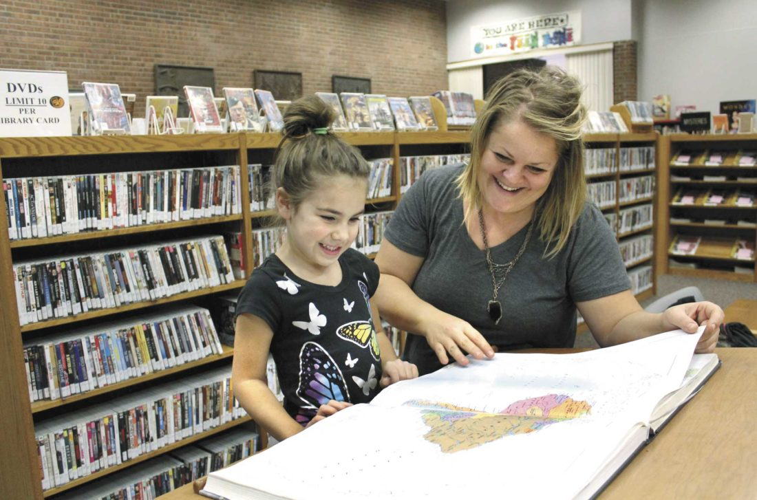 From left, Alise and Ahren Crotty look at an atlas at the Dickinson County Library in Iron Mountain. The library Tuesday announced a crowdfunding effort to help pay for a major redesign of the building's interior, including improved reading space and lighting. (Theresa Proudfit/Daily News photo)