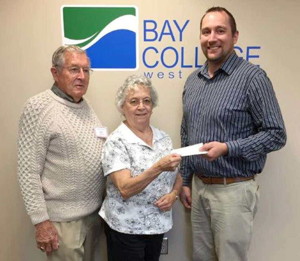 Ben Determan, left, president of Bay West LIFE and Judi Trumbley, treasurer of Bay West Life, present a scholarship donation to Kevin Carlson, vice president of Finance, Training & Development at Bay College.
