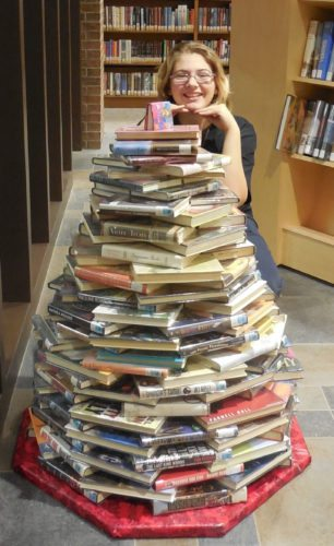 Tamera Jaeger poses with the Dickinson County Library's 2016 Book Lovers' Tree.