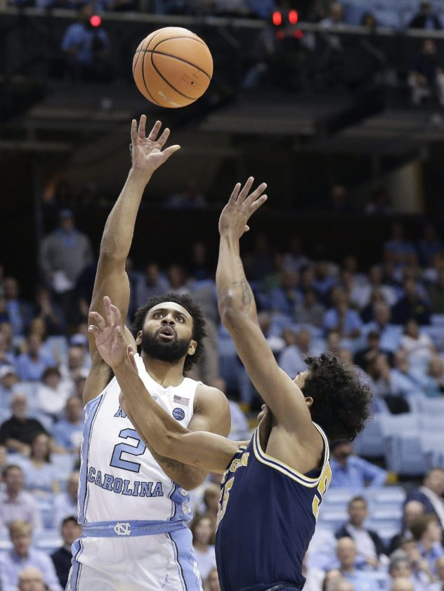 North Carolina's Joel Berry II (2) shoots while Michigan's Eli Brooks defends on Wednesday, Nov. 29, 2017, in Chapel Hill, N.C. (AP Photo/Gerry Broome)