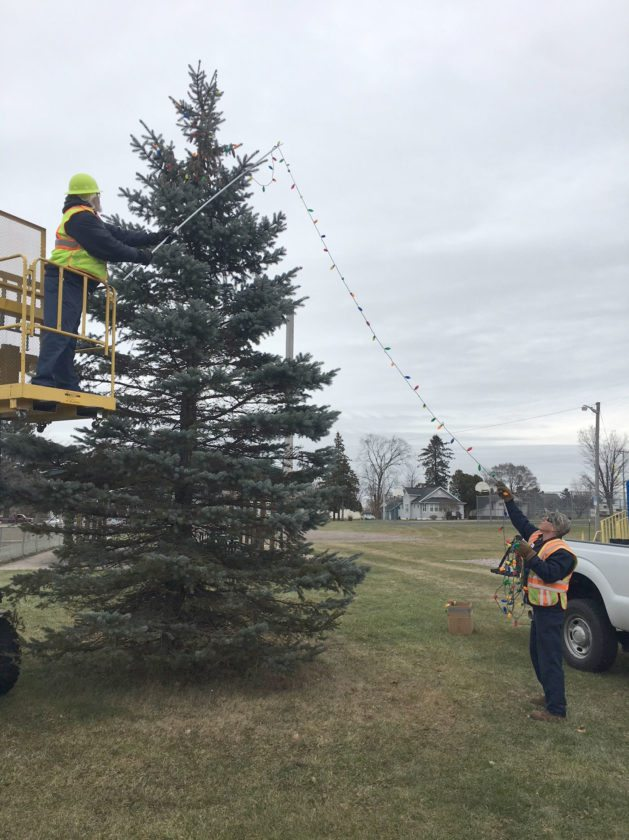 Jay Davis photo Breitung Township Department of Public Works employees Bill Bailey, left, and Chris Wilcox decorate a tree near the pavilion in the Quinnesec Park and Recreation Complex.
