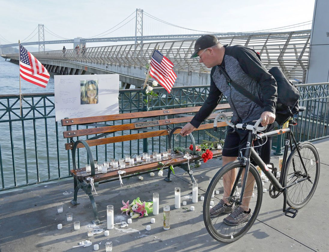 AP Photo/Ben Margot Craig Warner of Palo Alto, Calif., leaves a bell at a memorial site for Kate Steinle on Pier 14 Friday in San Francisco. In this fiercely liberal city, city leaders remained attached to San Francisco's sanctuary city status despite a not guilty verdict in a killing that sparked feverish immigration debates because the man who fired the gun was in the country illegally after being deported five times.