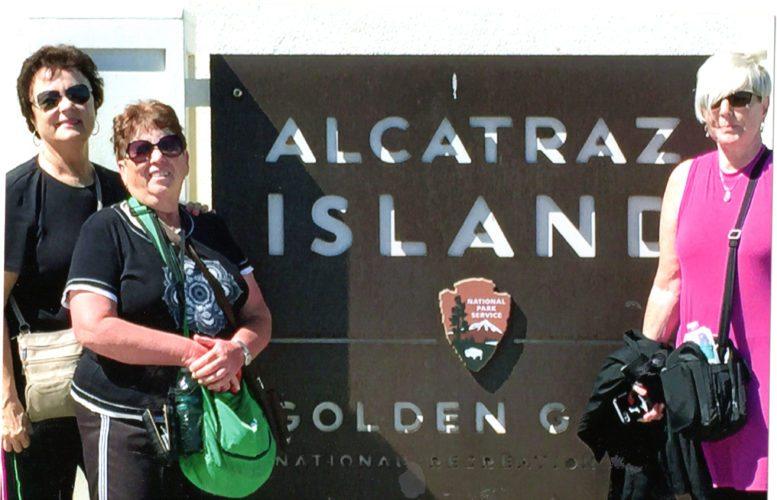 Members of the On the Road TravelGroup Susan Wilson, Judy Ball, and Jodi Farrington pose at Alcatraz Island sign.