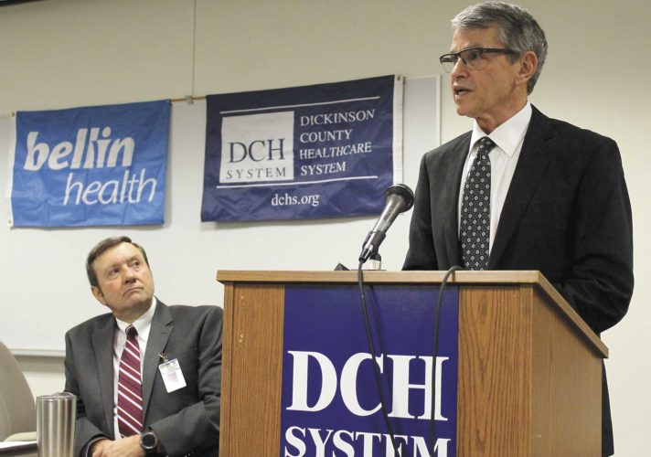 Dickinson County Healthcare Systems Administrator and CEO John Schon, left,  listens as Bellin Health CEO George Kerwin discusses the planned acquisition of DCHS by the Green Bay, Wis.-based medical provider. (Theresa Proudfit/Daily News photo)