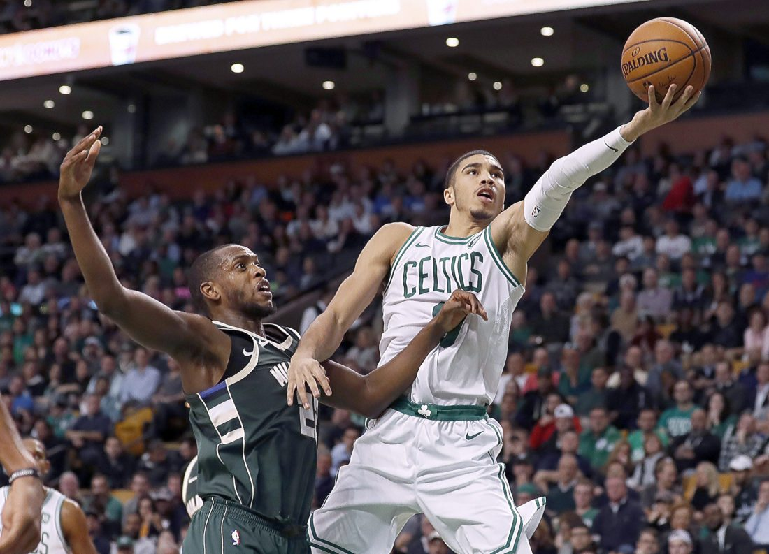 Boston Celtics' Jayson Tatum goes to the basket past Milwaukee Bucks' Khris Middleton on Monday, Dec. 4, 2017 in Boston. (AP Photo/Winslow Townson)
