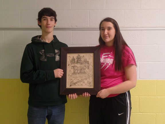 Florence High School students Kaden Schuls, left, and Taylor Schuls show a drawing done by their father, James, a 1994 FHS graduate. The lost drawing was recently discovered during a renovation of the school.